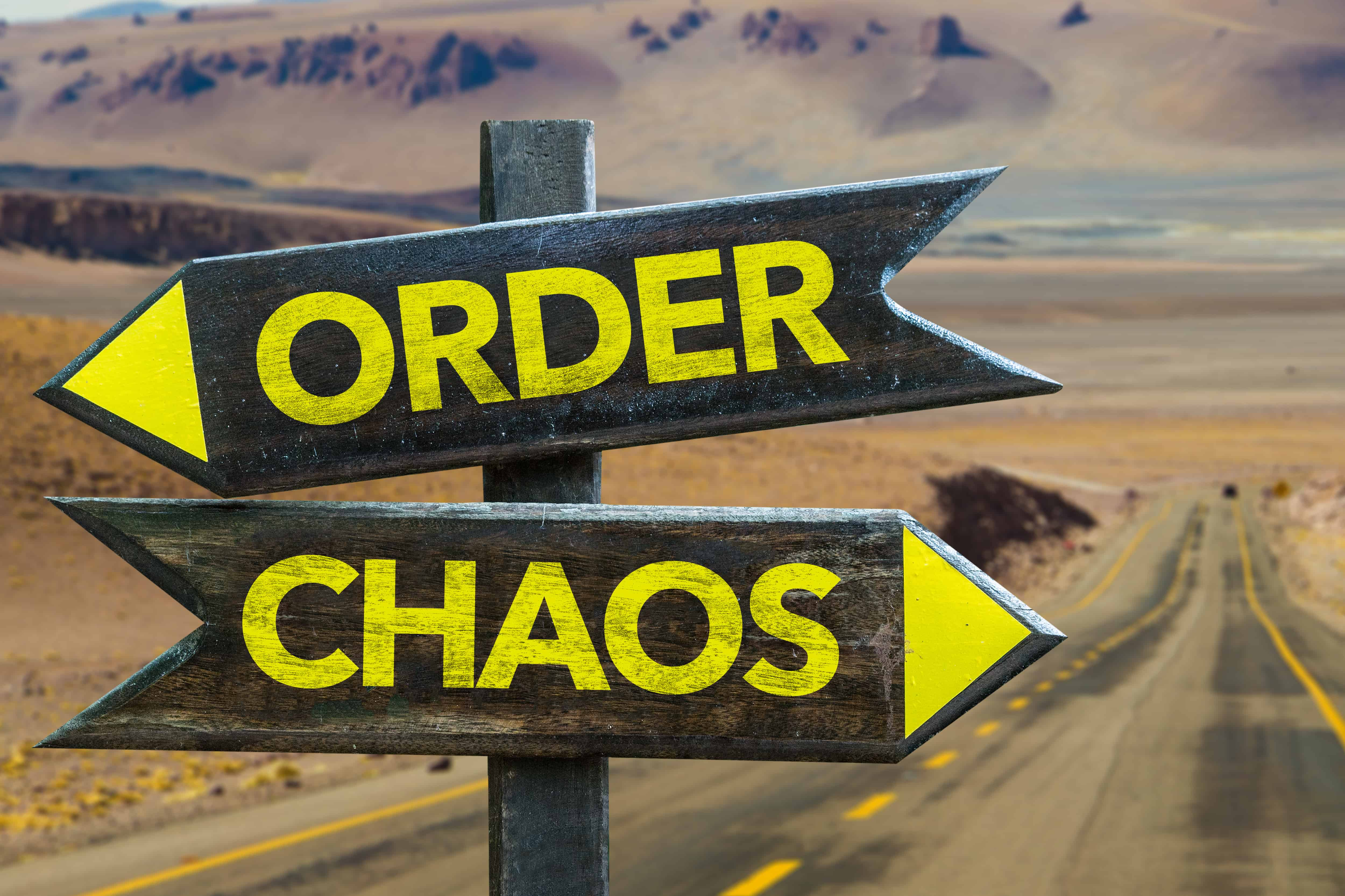 Order - Chaos signpost in a desert road background